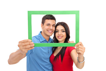 Young couple posing behind a green picture frame