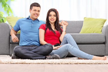 Couple posing seated on a carpet by a sofa at home