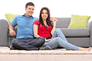 Young couple posing seated on a carpet by a sofa