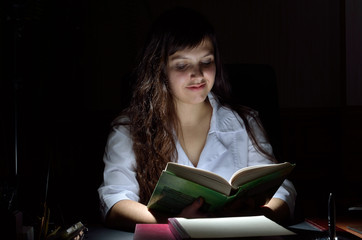 A young scientist with a book in the darkness