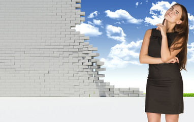 Thoughtful businesswoman in dress looking up. Dilapidated brick