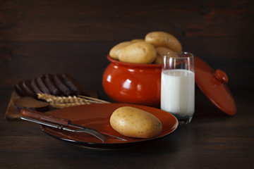 Fresh potatoes in a clay plate on a background of the dark woode