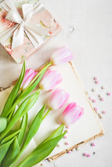 Pink tulips with gift box over white wooden table