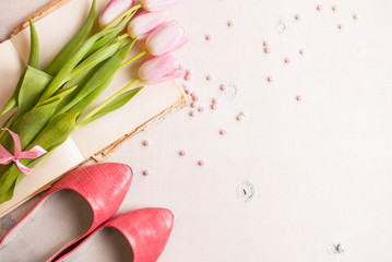 Pink tulips with women`s shoes over white wooden table. Spring c