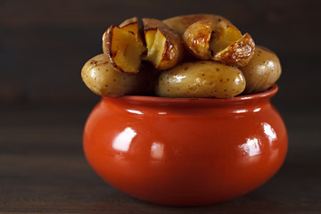 Baked potato in a clay pot on a background of the dark wooden su