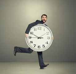 man holding big clock and running