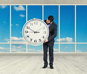 man with big white clock in empty room