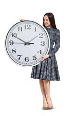 pretty woman looking at big clock