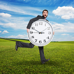 scared man holding big white clock
