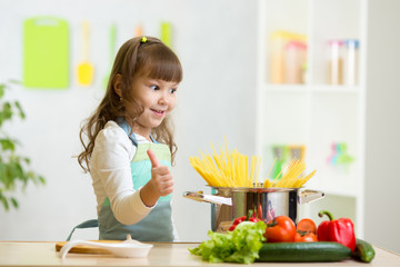 child girl playing cook and preparing spaghetti