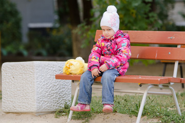 Gloomy girl in autumn clothes sitting on a bench
