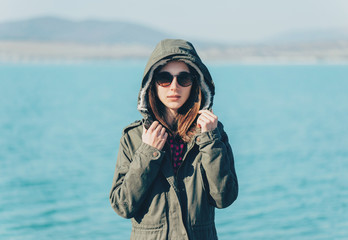 Girl in a jacket with hood on the coast