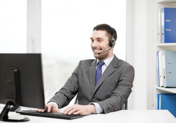 helpline operator with headphones and computer
