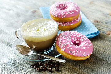 Cup of coffee with pink glazed donuts on wooden background