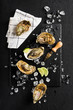 Fresh oysters on a black stone plate top view - 78314700