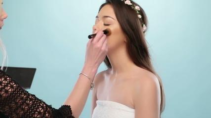 eautiful young woman having her makeup done
