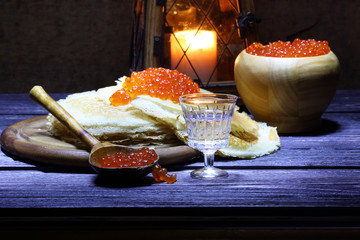 Pancakes with red caviar and a wine-glass of vodka and an old la