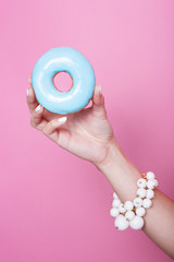 Women hand hold colorful donut
