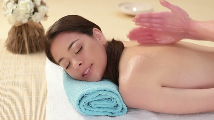 Peaceful brunette enjoying a back massage