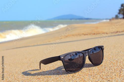 Leinwanddruck Bild Sunglasses on the beach