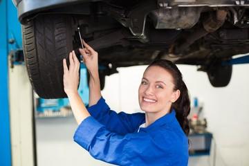 Smiling mechanic adjusting the tire