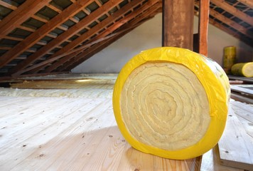 A roll of insulating glass wool on an attic floor