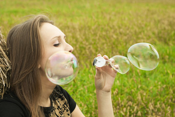 young girl sitting on the grass and blowing soap bubbles