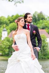 Hochzeitspaar im Park, Bräutigam umarmt Braut