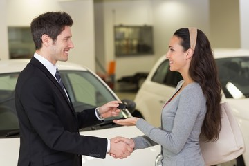 Businessman giving car key while shaking a customer hand