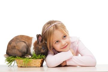 Beautiful girl with cute bunny in grass