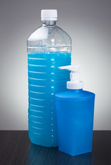 blue liquid soap on the table over grey background