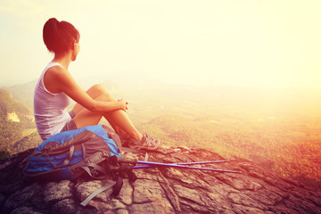 woman hiker enjoy the view at on mountain peak rock
