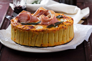 Pasta pie with cheese sauce and sage