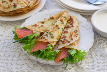 Thin rolled pancakes, crepes with salmon. Traditional Russian