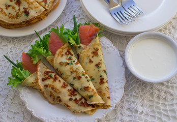 Thin rolled pancakes, crepes with salmon, . Traditional Russian