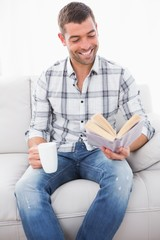 A smiling man reading a book with a cup