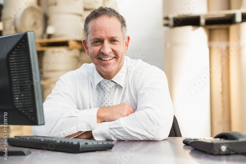Smiling manager with arms crossed sitting at desk