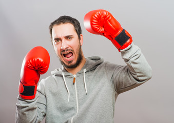 Angry man wearing red boxing gloves punching in air