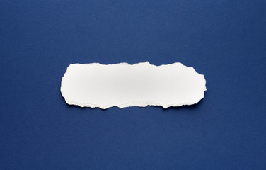 A piece of torn paper on a blue background