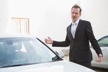 Businessman looking his car engine after breaking down