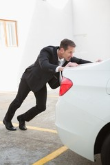 Businessman pushing his broken down car