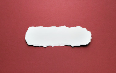 A piece of torn paper on a red background