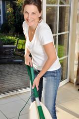 Frau mit Staubsauger bei Hausarbeit