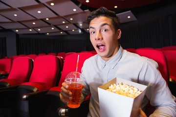 Surprised young man watching a film