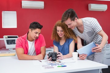 Smiling students working with camera and tablet