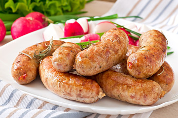 Homemade sausages baked in the oven and salad