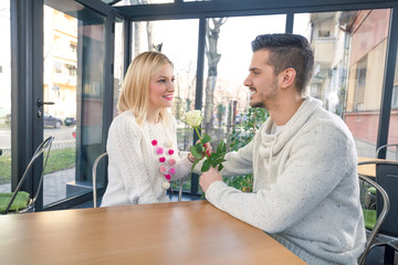 Romantic young man giving white rose to his girlfriend