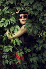 girl wearing red sun glasses over foliage background