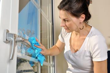 Frau bei Hausarbeit putzt Fenster mit Fenstertuch