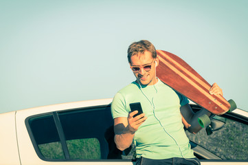 Young hipster man wth smartphone and music next his car